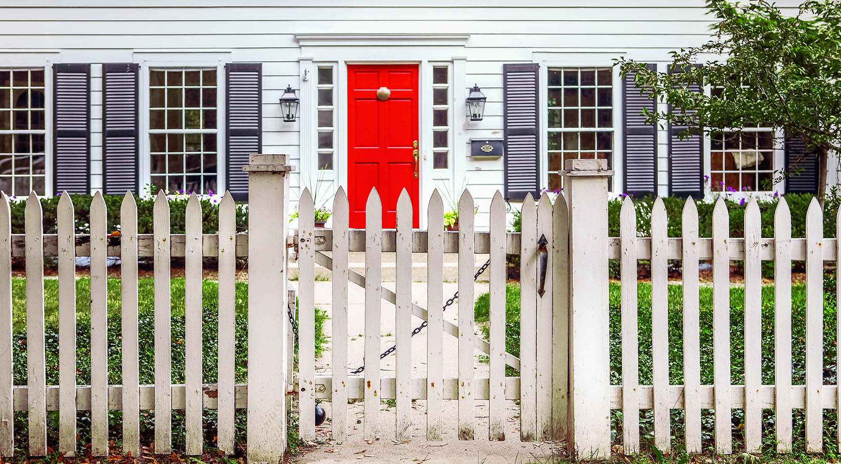 White picket fence around home with red door