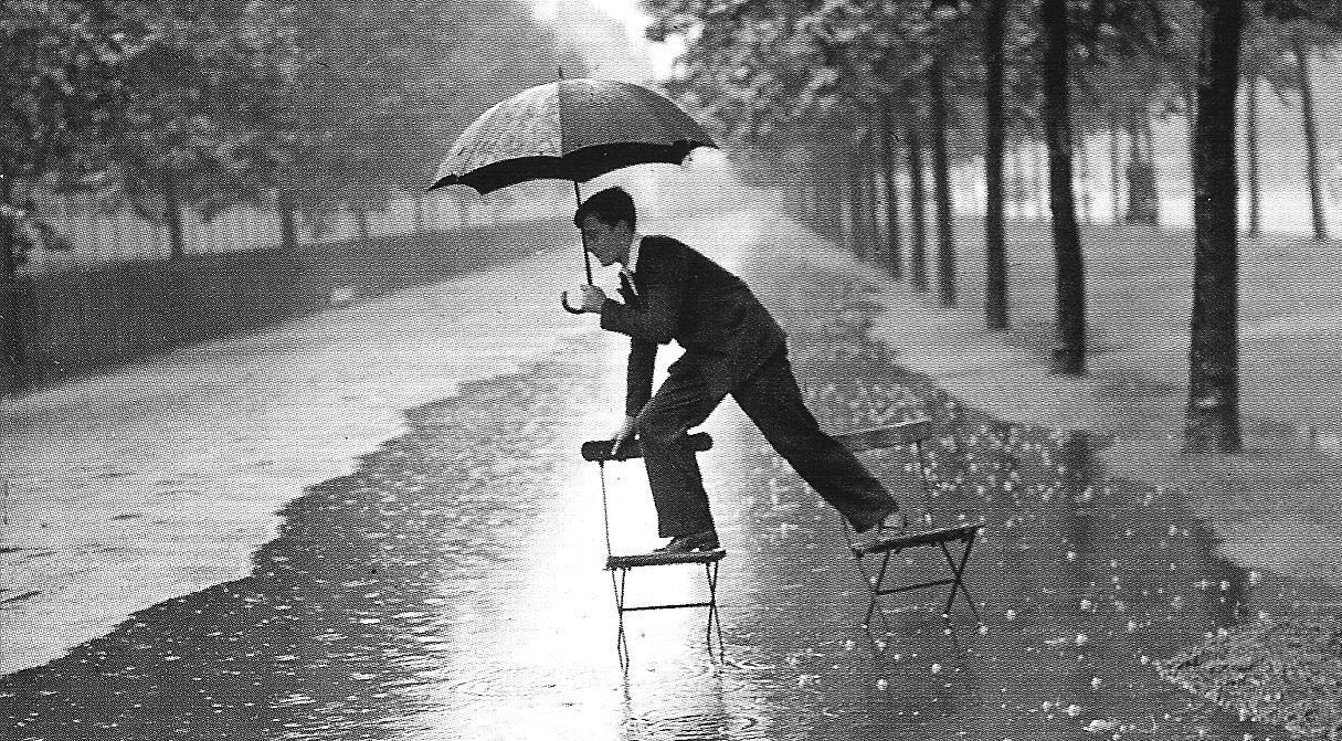 Man in the rain standing on two chairs