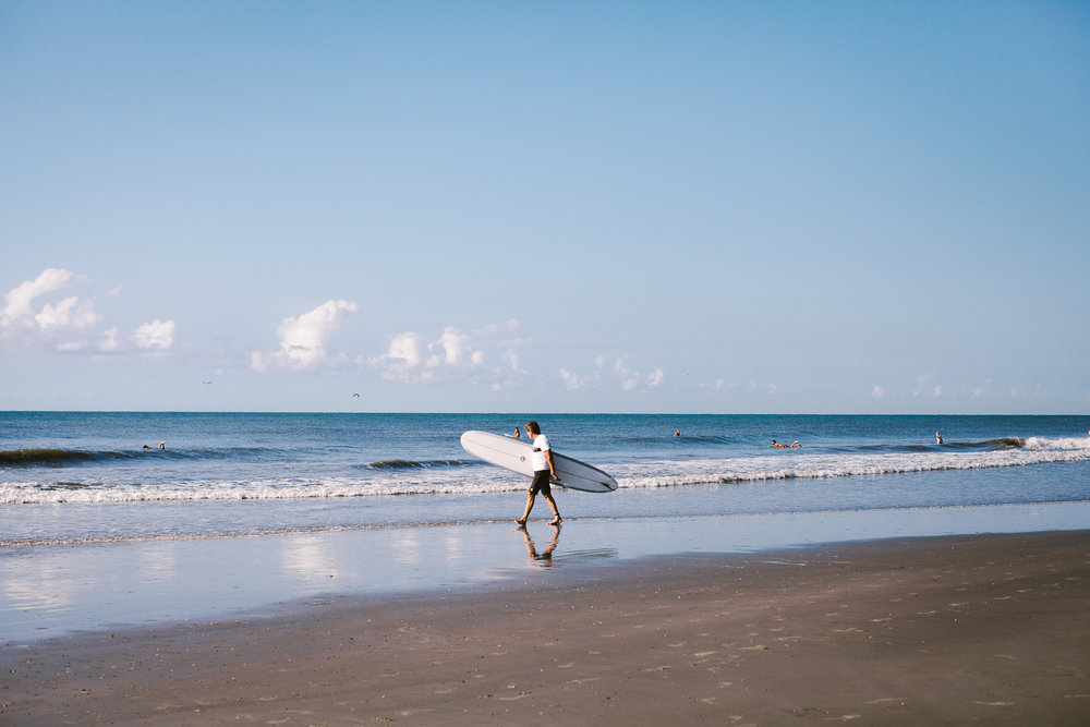 Man walking on the beach with a surf board